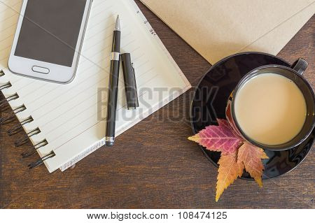 Mobile phone, coffee with autumn leaves, notebook and craft paper on wooden deck