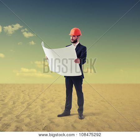 builder in orange hat reading blueprint in desert on the sand