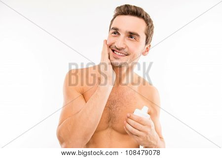 Handsome Man Holding Lotion After Shave Smearing Cheek