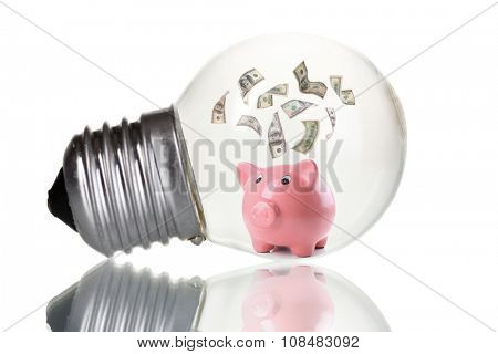 Piggy bank with money inside light bulb, isolated on white