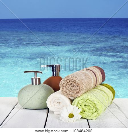 Soft towels with dispenser and flower on sea background