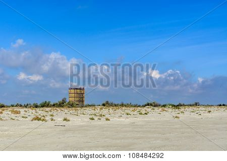 Sandy Beach With The Building And Grass In The Background.  Land