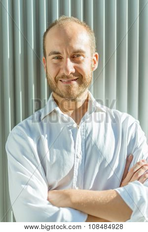 Portrait of a smiling man leaning against a wall of corrugated iron