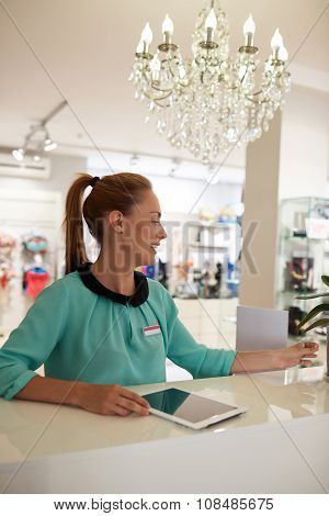 Portrait of a young beautiful businesswoman using touch pad during work day in her fashion shop