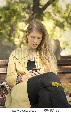 Blonde Girl Writing Text While Leaves Are Falling