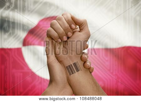 Barcode Id Number On Wrist Of Dark Skinned Person And National Flag On Background - Greenland