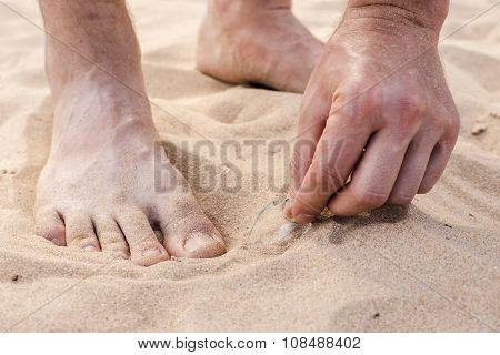 Man Lifts Shard Of Broken Glass Littered On The Beach