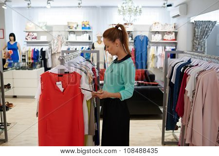 Beautiful business woman checking availability of stock of trendy dresses