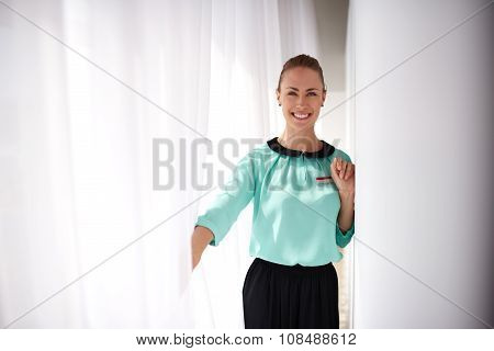 Female service worker with beautiful smile standing in modern interior copy space area