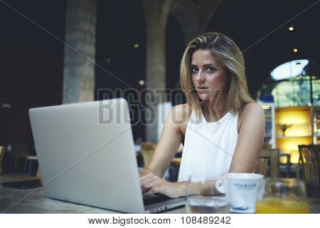 Beautiful female student siting front open laptop computer in modern coffee shop interior