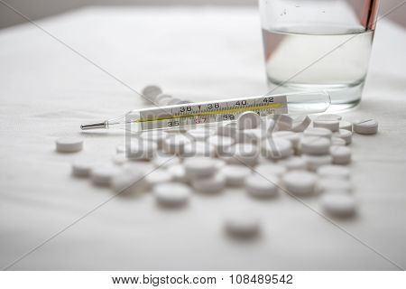 Medical Thermometer And On The Table White Pills And Glass Of Water