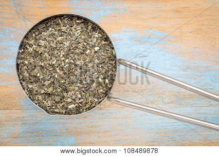 dried wakame seaweed - top view of a metal measuring scoop against painted wood