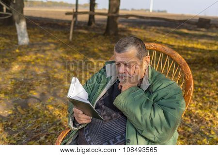 Senior man sitting in wicker chair and reading diary