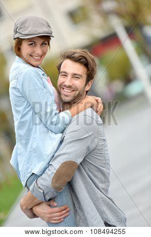 Cheerful man lifting girl up in arms