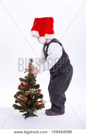 boy with santa hat decorate christmas tree