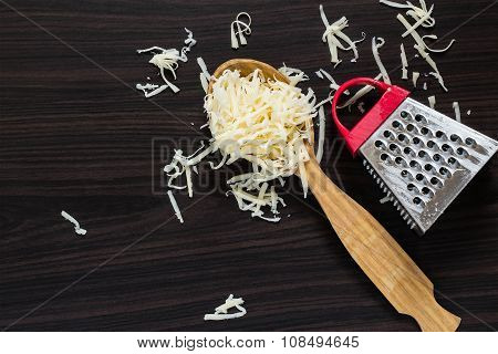 Grated Cheese In The Spoon And Grater