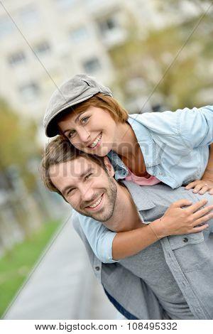Portrait of man giving piggyback ride to girlfriend