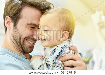 Portrait of young man holding baby in arms