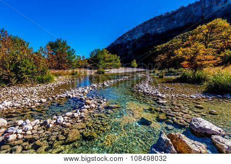 Bright Beautiful Fall Foliage On The Rocky Crystal Clear Frio River in Texas