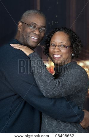 Portrait of a loving, mature, African AMerican couple with Christmas lights and a nighttime windows in the background.