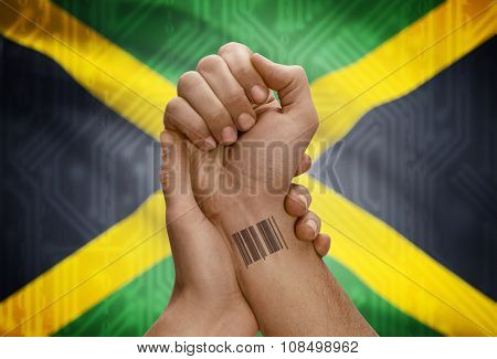 Barcode Id Number On Wrist Of Dark Skinned Person And National Flag On Background - Jamaica