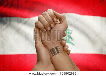 Barcode Id Number On Wrist Of Dark Skinned Person And National Flag On Background - Lebanon