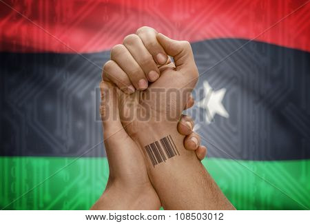 Barcode Id Number On Wrist Of Dark Skinned Person And National Flag On Background - Libya