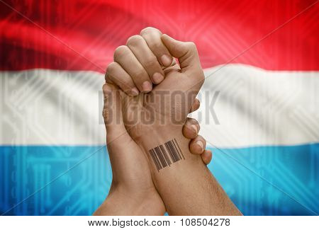 Barcode Id Number On Wrist Of Dark Skinned Person And National Flag On Background - Luxembourg