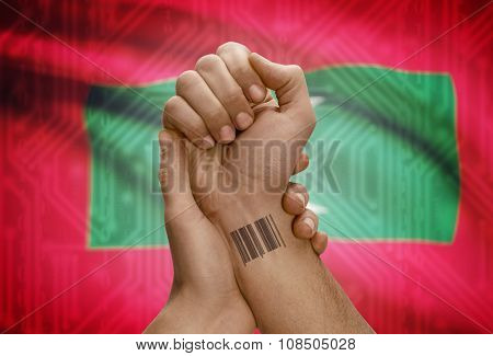 Barcode Id Number On Wrist Of Dark Skinned Person And National Flag On Background - Maldives