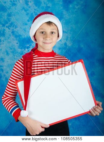 Smiling Child In Red Santa Hat Holding White Board