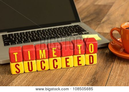 Time to Succeed written on a wooden cube in a office desk