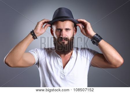 Portrait of handsome man in hat standing , isolated on grey background