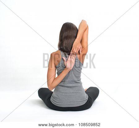 Long haired beautiful smiling woman doing a Yoga pose (ansana). Isolated on white background.