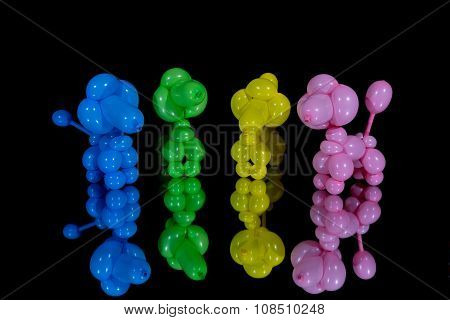 Four Colorful Balloon Dog Poodles On A Mirror