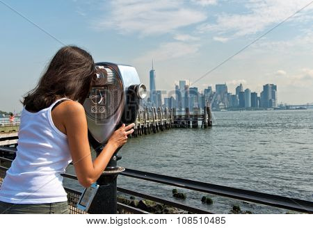 Rear View of Woman Peering Through Binocular View Finder at New York City Skyline from Pier on Sunny Day on Liberty Island, New York, USA