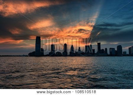 Skyline of Midtown Manhattan from Across Hudson River, New York City, New York, USA - Silhouette of Skyscrapers Backlit by Sunset and Dramatic Clouds