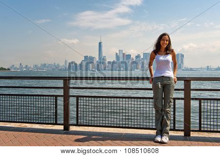 Portrait of Smiling Young Woman Leaning Against Railing on Liberty Island with View of New York City Skyline in Background