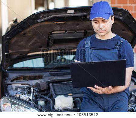 Mechanic checking a car engine with his laptop