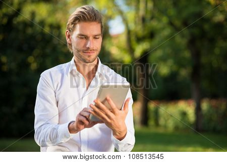 Portrait of a young man using his tablet outdoors