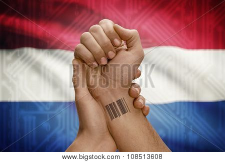 Barcode Id Number On Wrist Of Dark Skinned Person And National Flag On Background - Netherlands