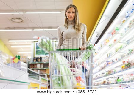 Young woman driving a shopping cart in a supermarket