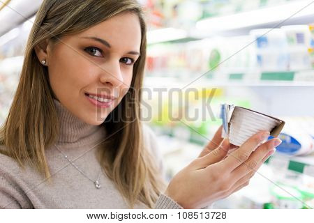 Smiling woman holding a product in a supermarket