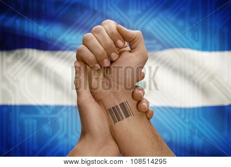 Barcode Id Number On Wrist Of Dark Skinned Person And National Flag On Background - Nicaragua