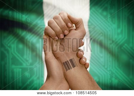 Barcode Id Number On Wrist Of Dark Skinned Person And National Flag On Background - Nigeria