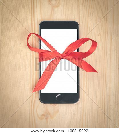Smartphone With White Blank Screen Tied With A Red Ribbon On Wooden Table