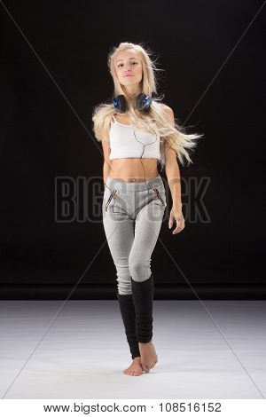 Fitness, sport, training and lifestyle concept - smiling woman standing on the floor in earphones.