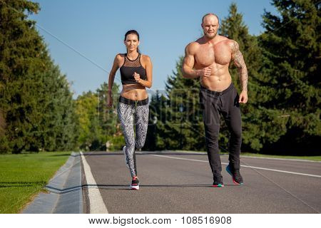 Young strong male and female  fitness models outdoors in beautiful landscape. Man and woman running in park