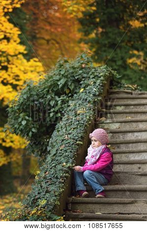 Children sitting on old stone stairs in the park