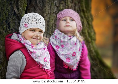Portrait of two kids in the park with a large tree trunk