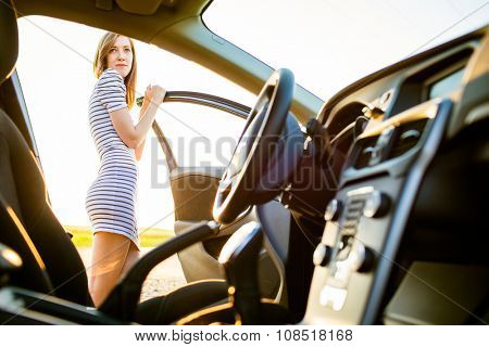 Portrait of a pretty, female teen driver, by her new car